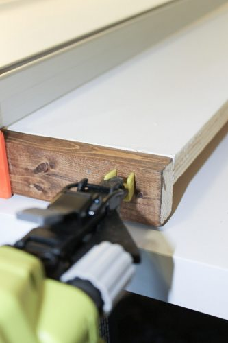 Attaching DIY wood sign frame pieces to sign backing with brad nailer and nails