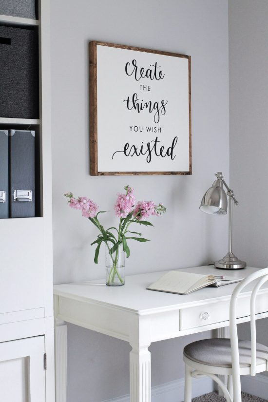 DIY wooden sign above desk on office wall