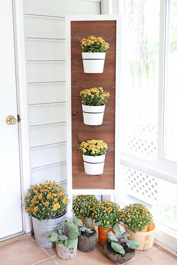 DIY plant stand decorated for fall with mums