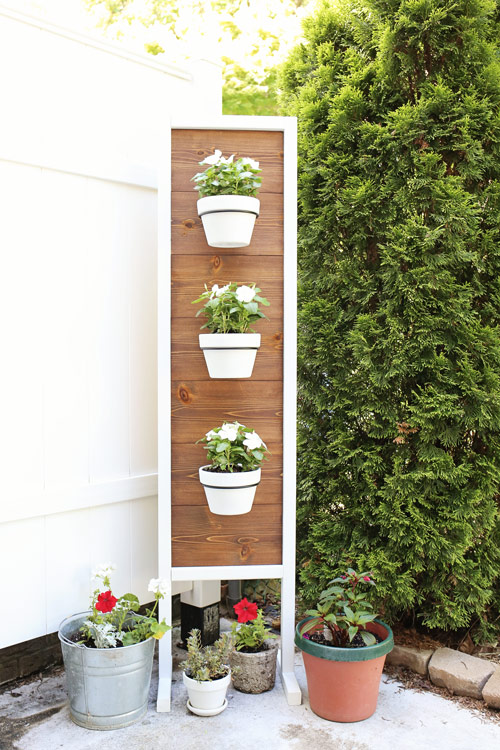 diy outdoor plant stand with flowers in front of fence and tree