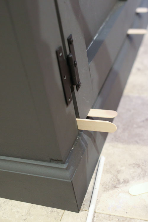 attaching doors to tv stand with hinges using popsicle sticks as spacers