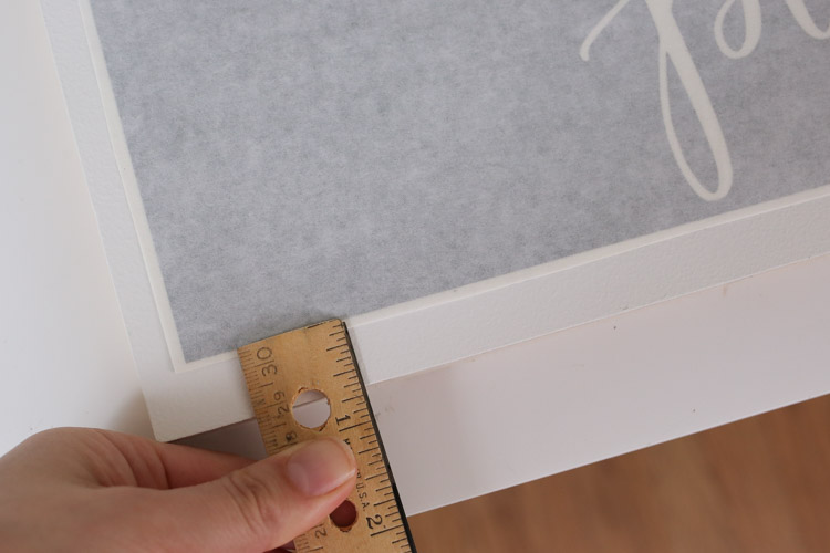 Center vinyl stencil on wood backing using a ruler