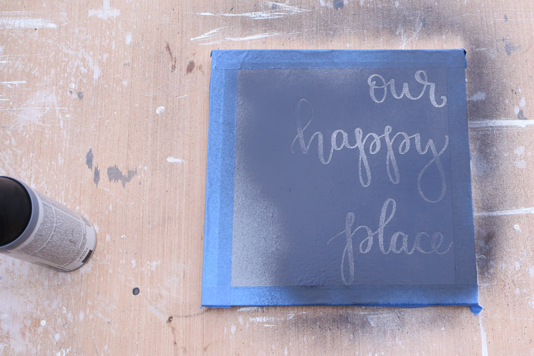 spray paint over vinyl stencil onto wood sign