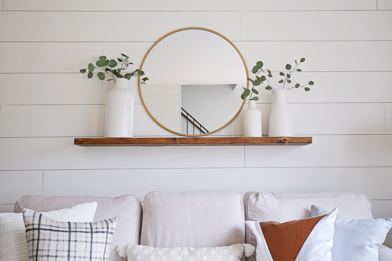 DIY wood Floating Shelf with modern round bras mirror, white ceramic vases, and ecualyptus branches