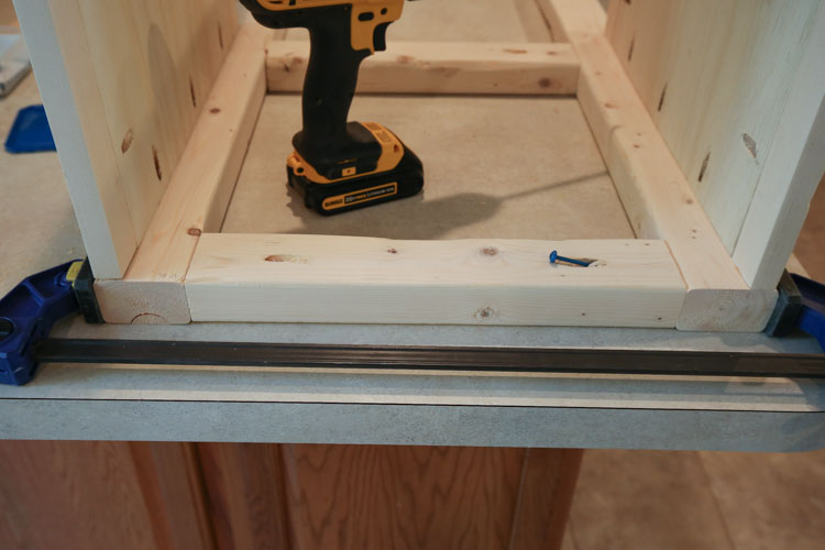 Attach back framing boards to bathroom vanity sides