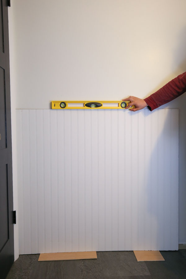 Beadboard panel being applied to a bathroom wall using a level