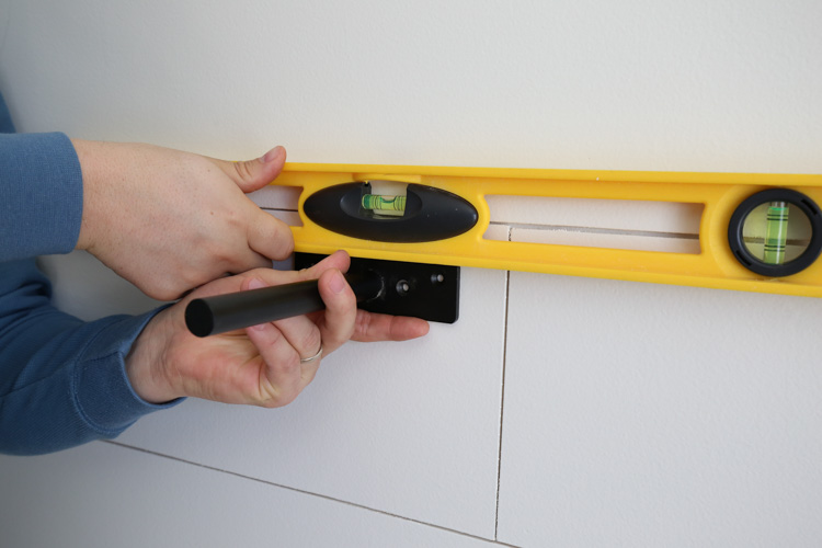 Holding a level on floating shelf bracket