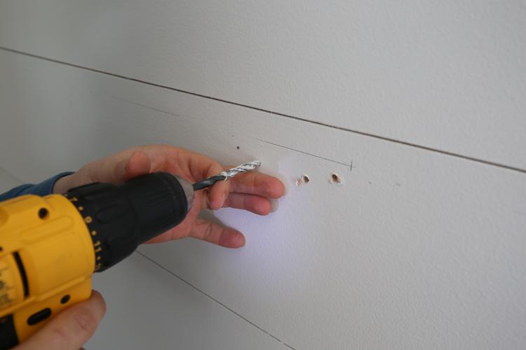 percer des trous pilotes sur le mur pour les supports de tablette flottants