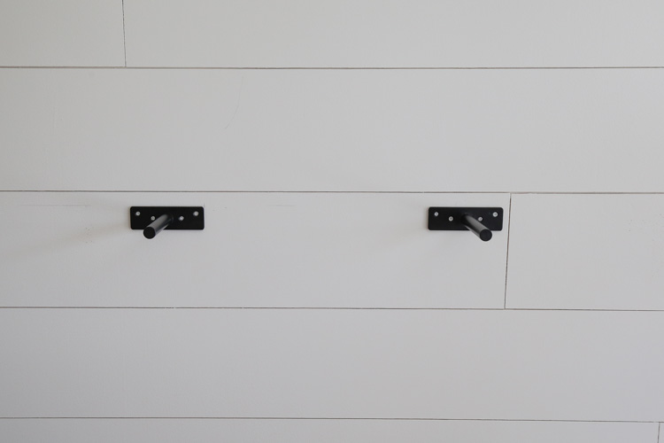 two heavy duty steel floating shelf brackets hung on the wall