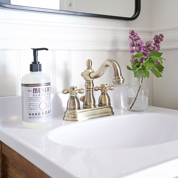 Antique brass bathroom faucet, Mrs. Meyer's Hand Soap, and Lilacs on bathroom vanity
