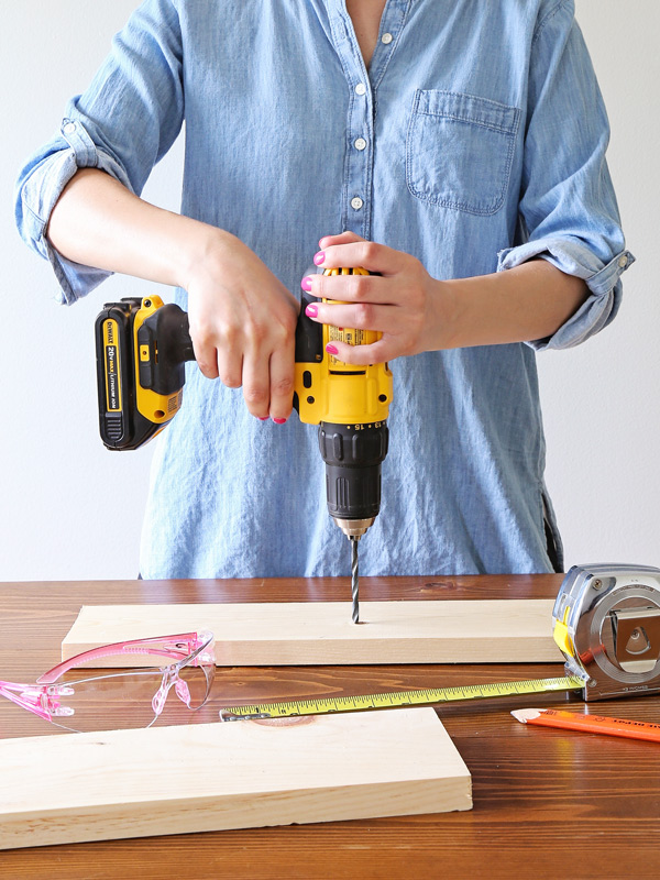 woman using a power drill which is a woodworking tool for beginners
