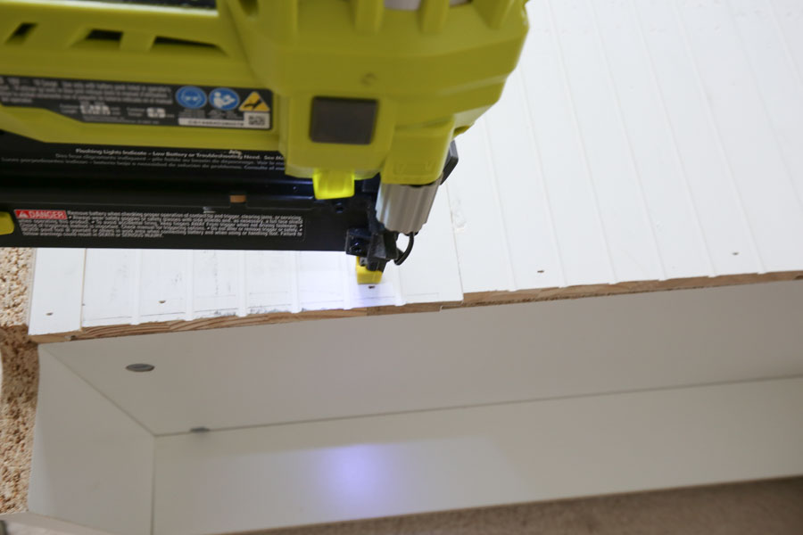Using a brad nailer to attach shiplap boards to back of bookcase