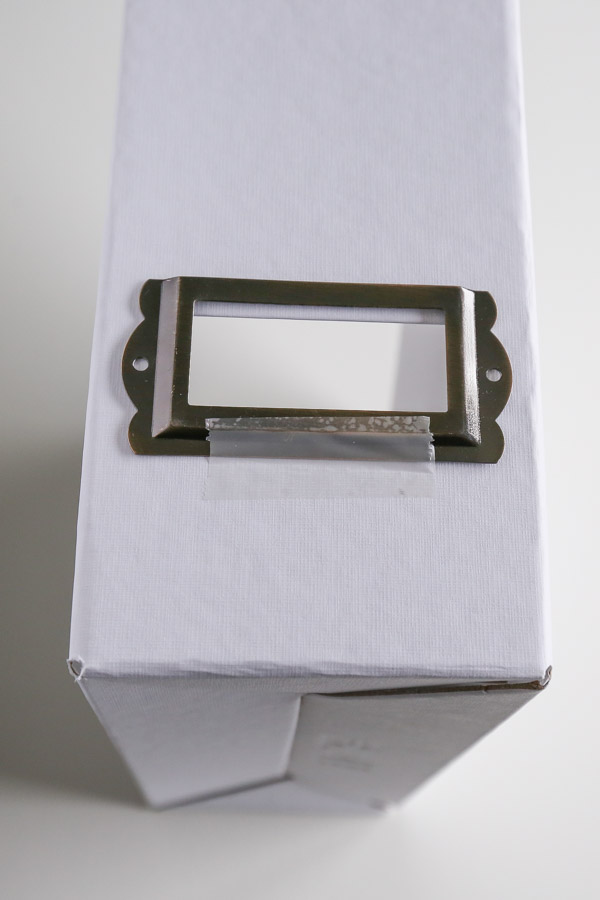 Metal card label holder taped in place on magazine holder