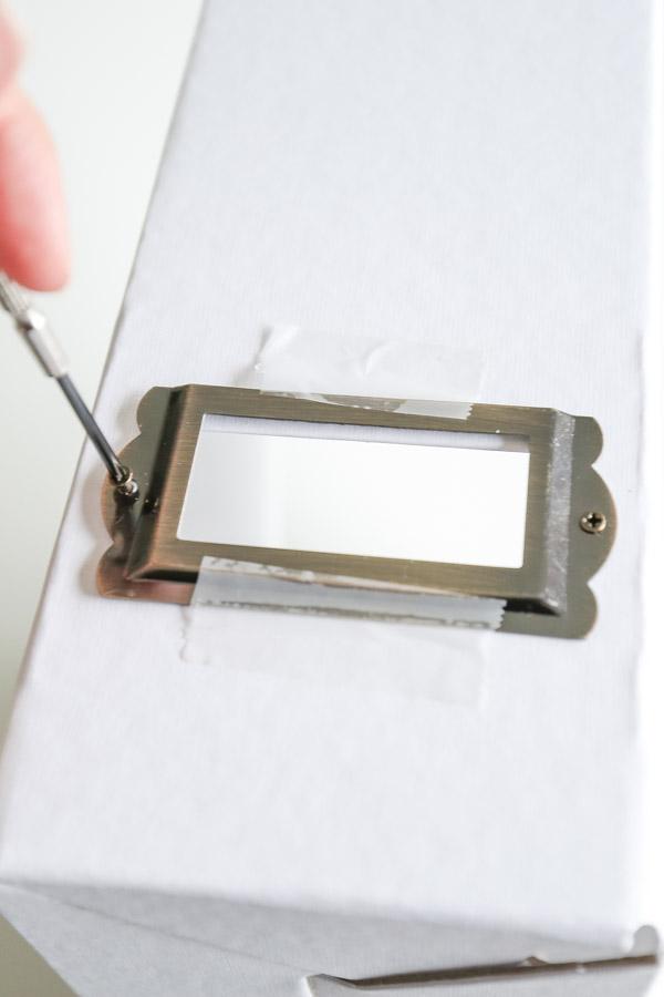 Screwing brass metal card label holder in place onto DIY magazine holder