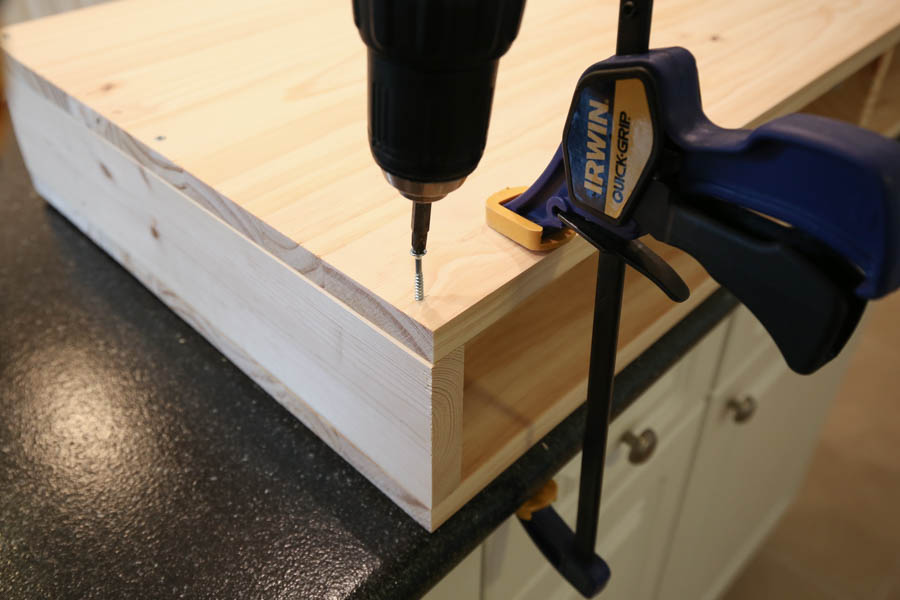 Attaching base wood panel board to makeup vanity top with a drill