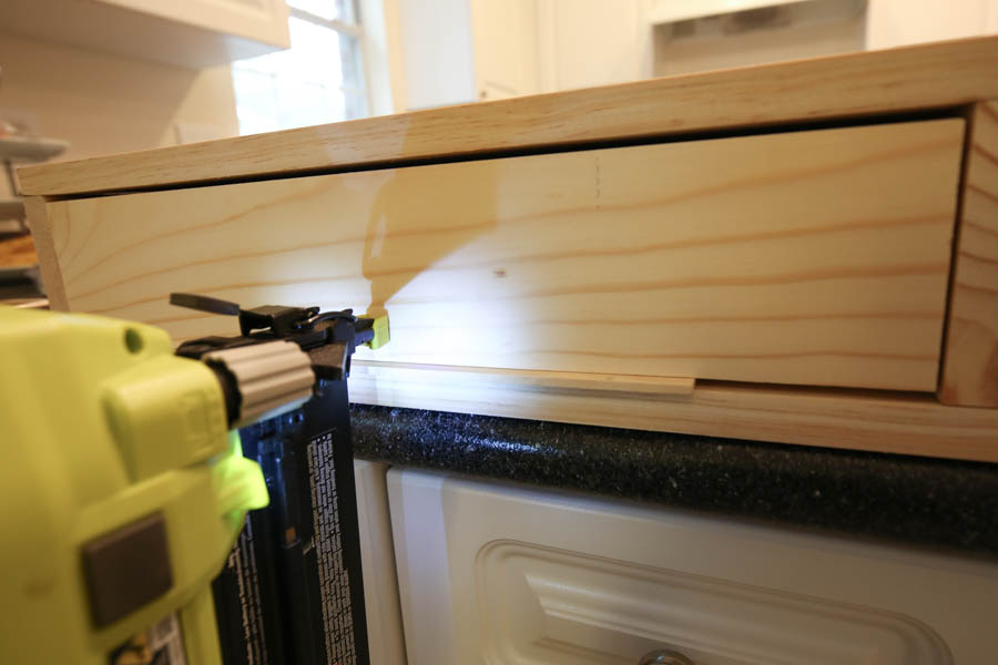 Attaching the drawer faces to the makeup vanity with a brad nailer from the front using a paint stick stirrer to hold in place
