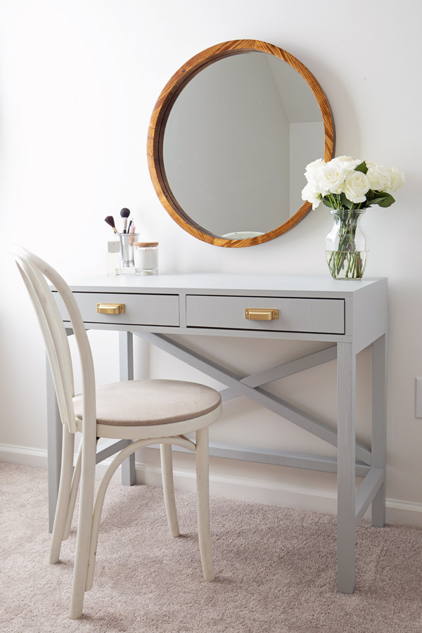DIY makeup vanity painted light grey with chair and round wood mirror
