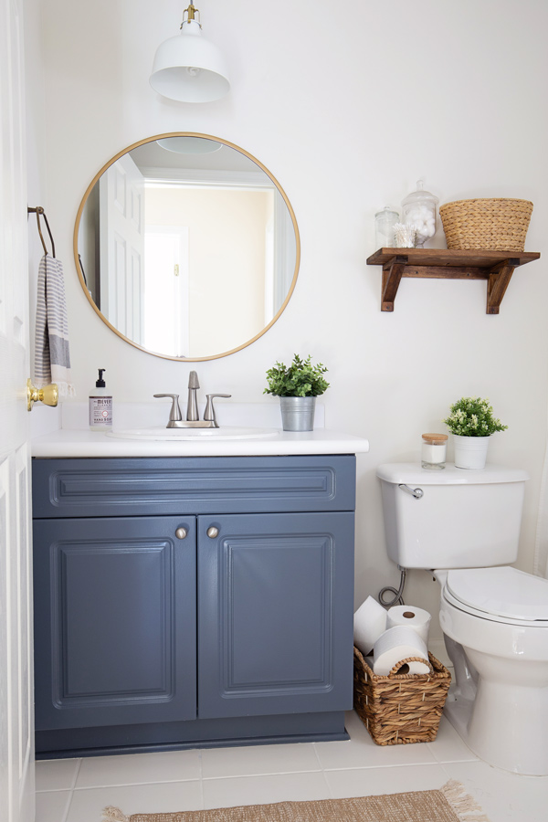 budget bathroom makeover with blue bathroom vanity, white walls, and round gold mirror