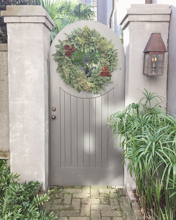 Christmas wreath with pinecones on grey fence door in Charleston for Christmas decor