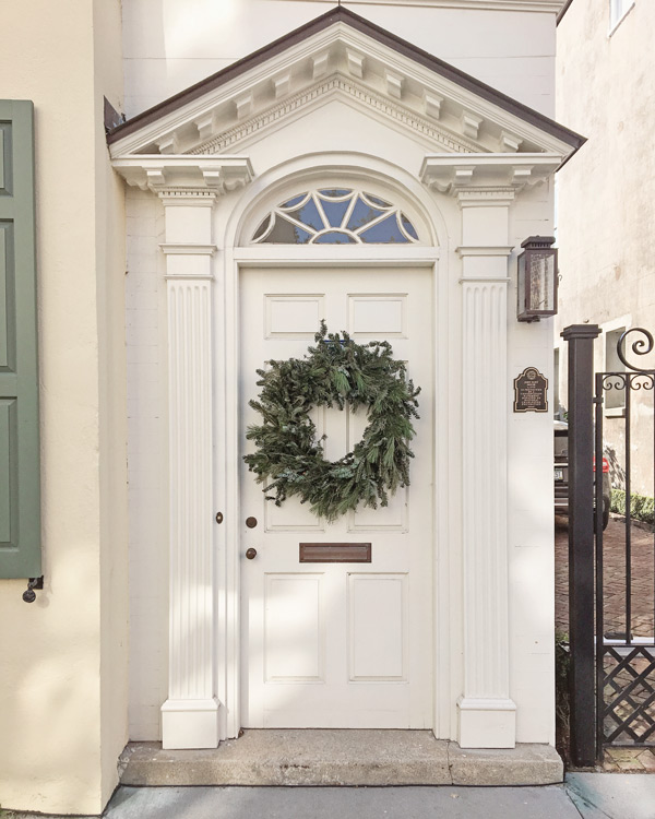 bushy green Christmas wreath on white front door in Charleston