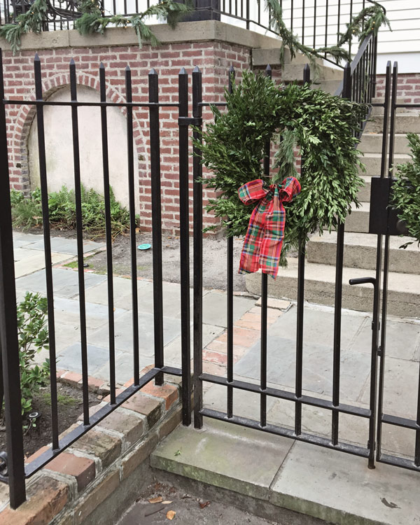 boxwood wreath with red plaid bow on iron fence in Charleston for Christmas decor