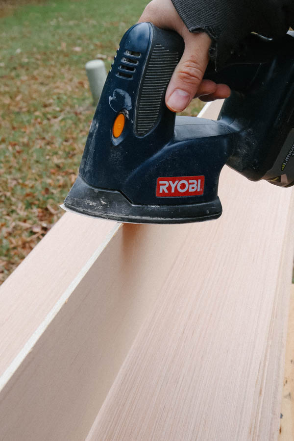 sanding edge of shiplap board with electric sander