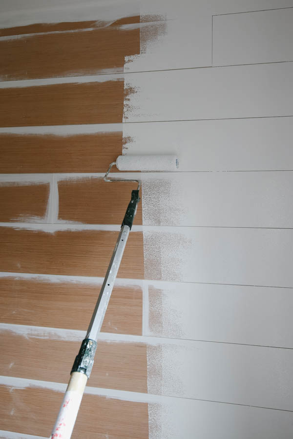 Rolling a shiplap wall with white paint and paint roller