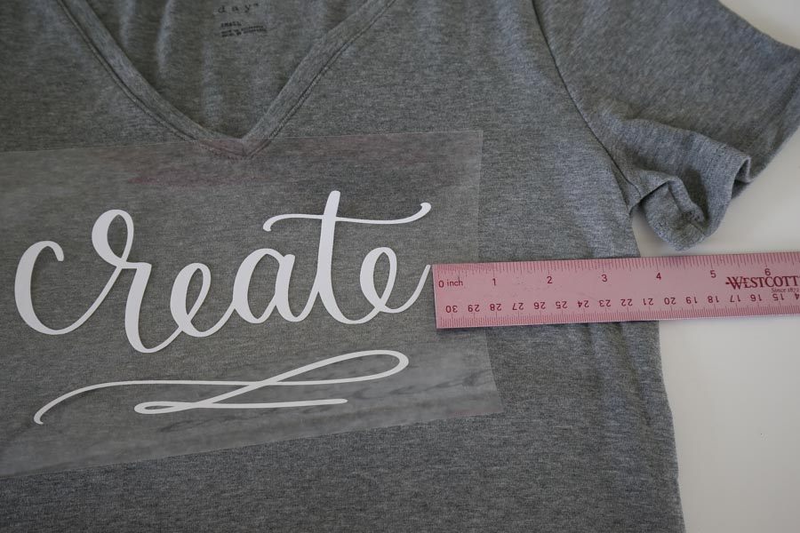 Lay design in place on the t shirt by eyeing placement and using a ruler