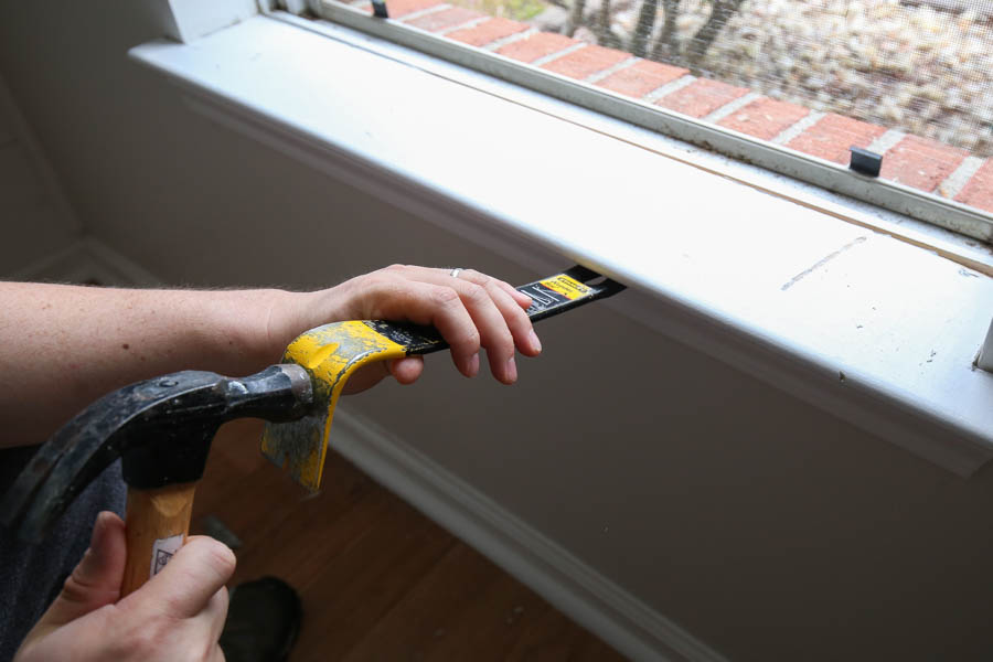 Remove old window sill with hammer and prybar