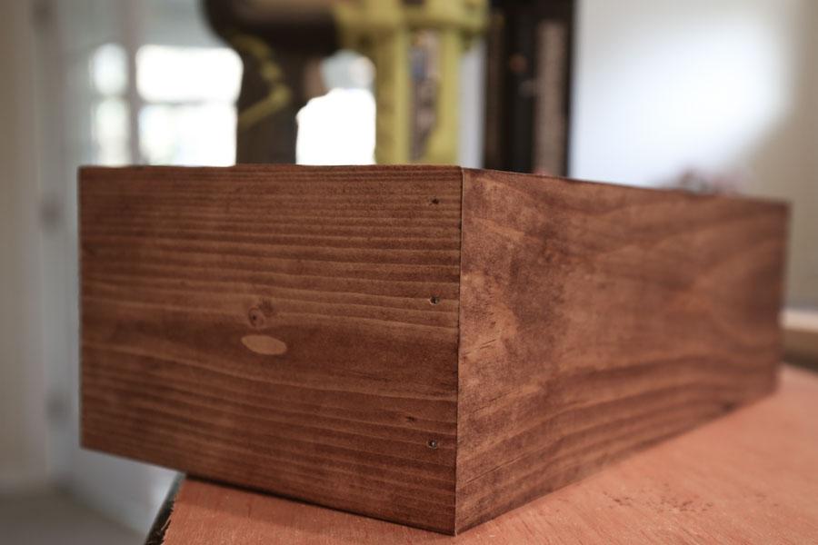 assembling DIY spring planter box with brad nails