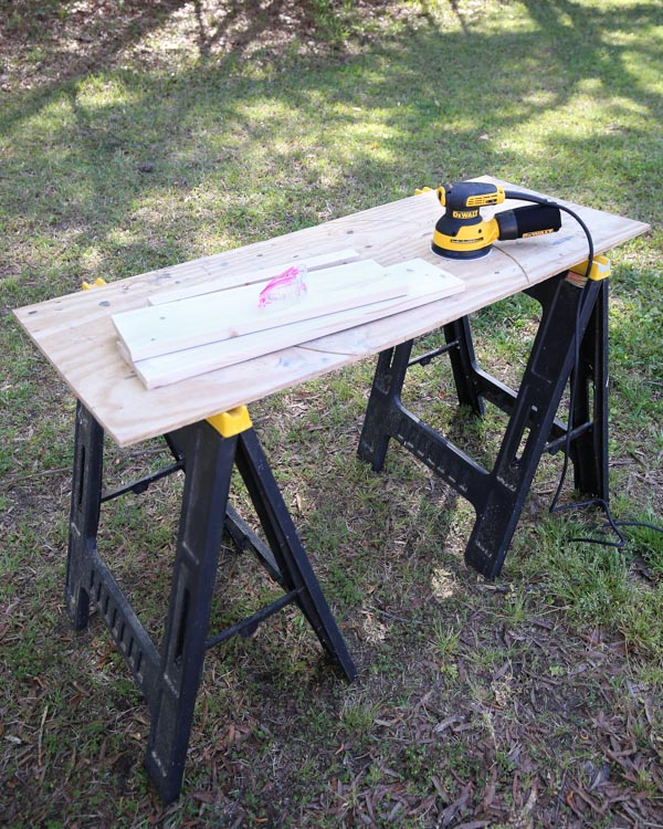 sawhorses wtih plywood set up as a work station for sanding wood