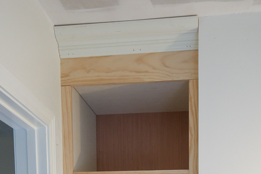 Install crown molding to the top of the DIY built in shelves with brad nails