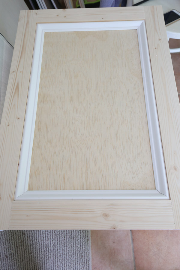 Add base cap molding to the front interior of the cabinet door frame with brad nails