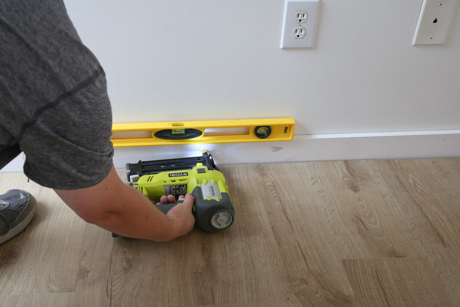 install new baseboard with level, brad nails, and brad nailer