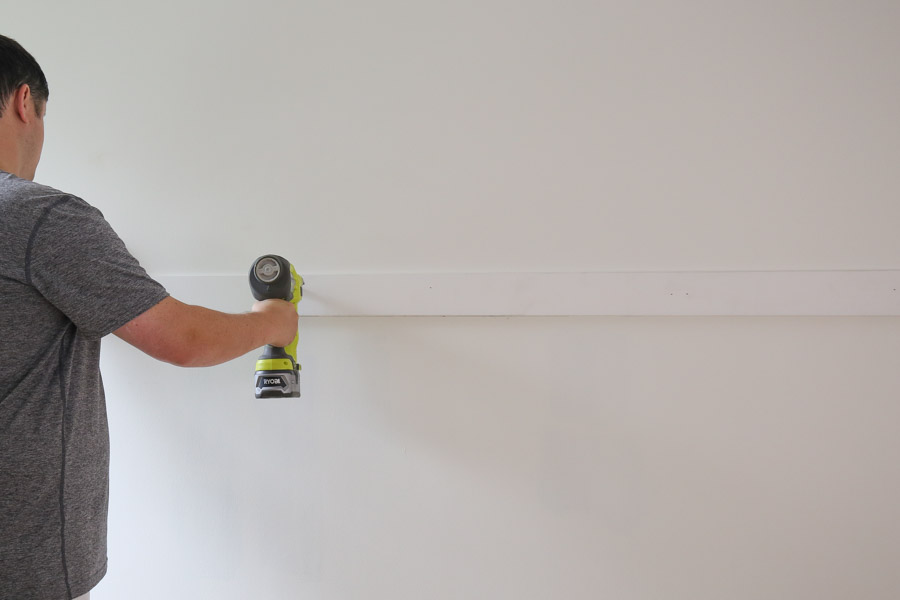 attaching middle board to wall with brad nailer for board and batten wainscoating