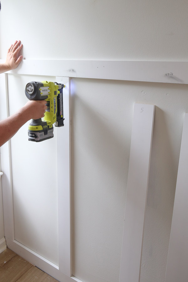 using a brad nailer to attach batten boards to wall for DIY board and batten