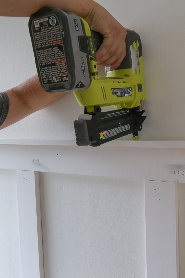 using a brad nailer to attach top 1x2 ledge board for diy board and batten accent wall