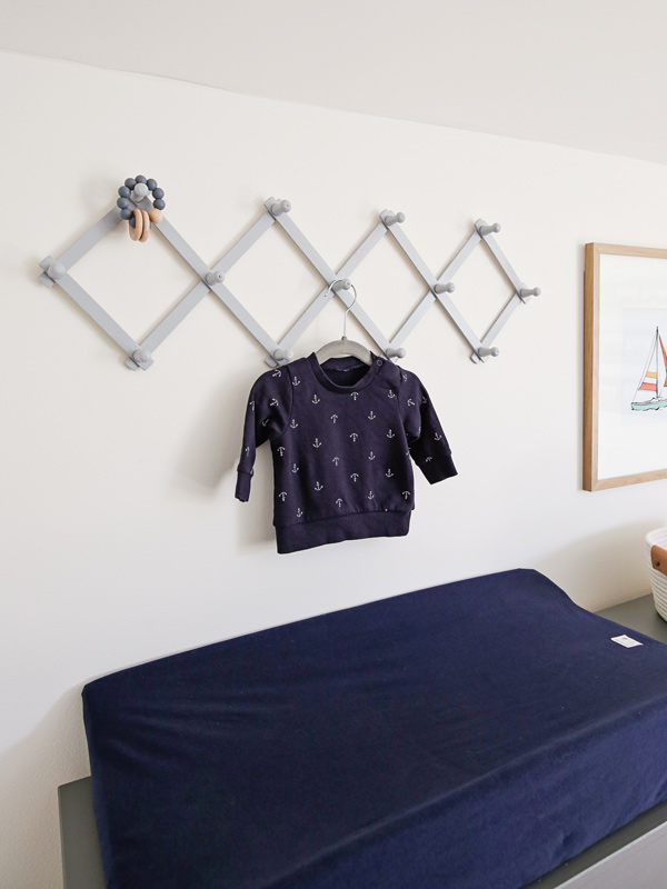 nursery changing station with accordion peg rack on wall