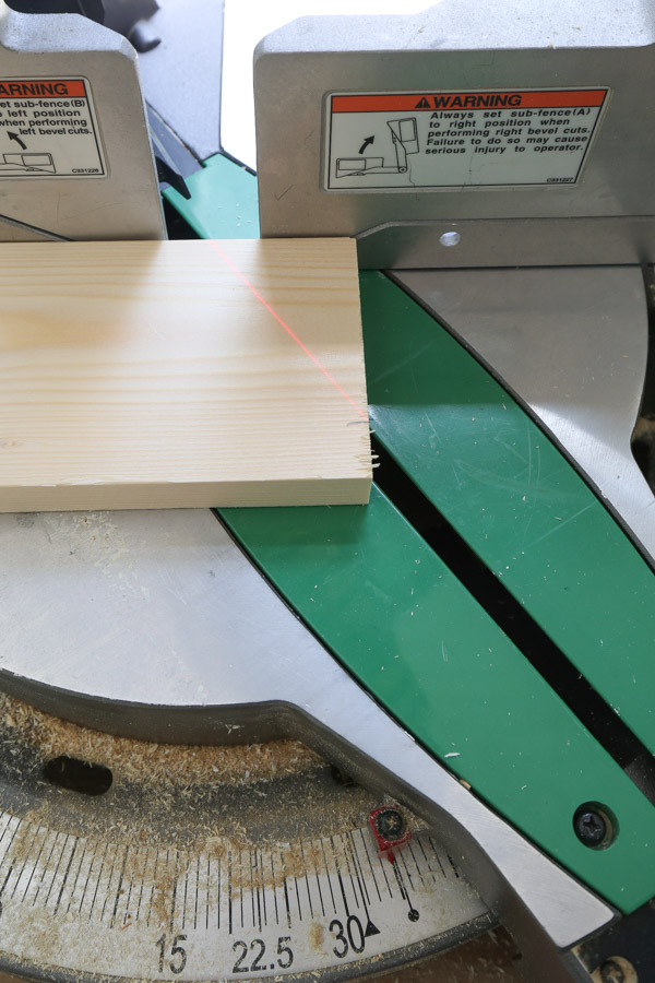 cutting lumber to size for DIY floating bookshelves using a miter saw