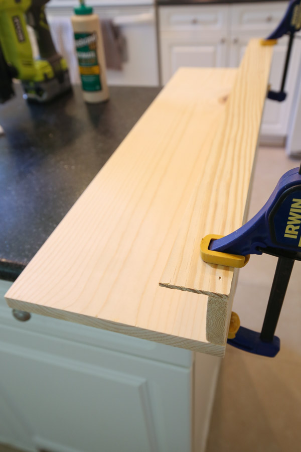 attach front board of DIY kids bookshelf with brad nailer and wood glue