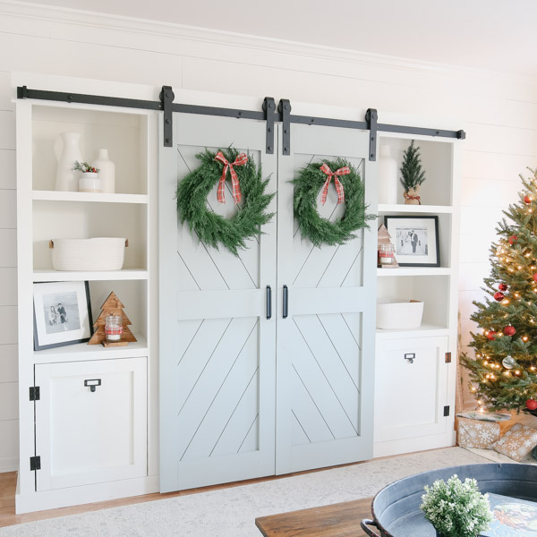 Christmas decor and Christmas wreaths on double barn door entertainment center