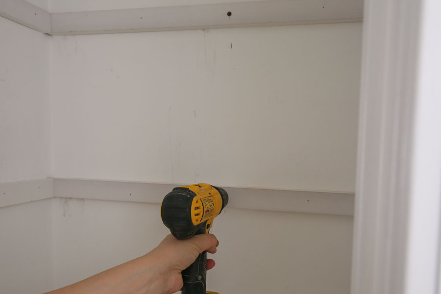 secure DIY pantry shelves support boards into pantry wall stud with a drill and screw