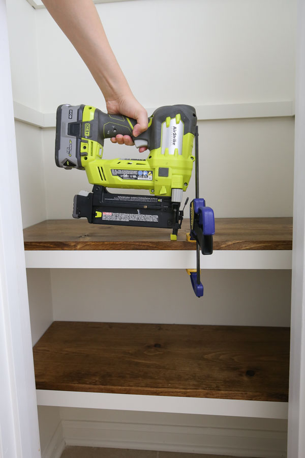 secure diy pantry shelves to front trim boards with brad nailer and clamp