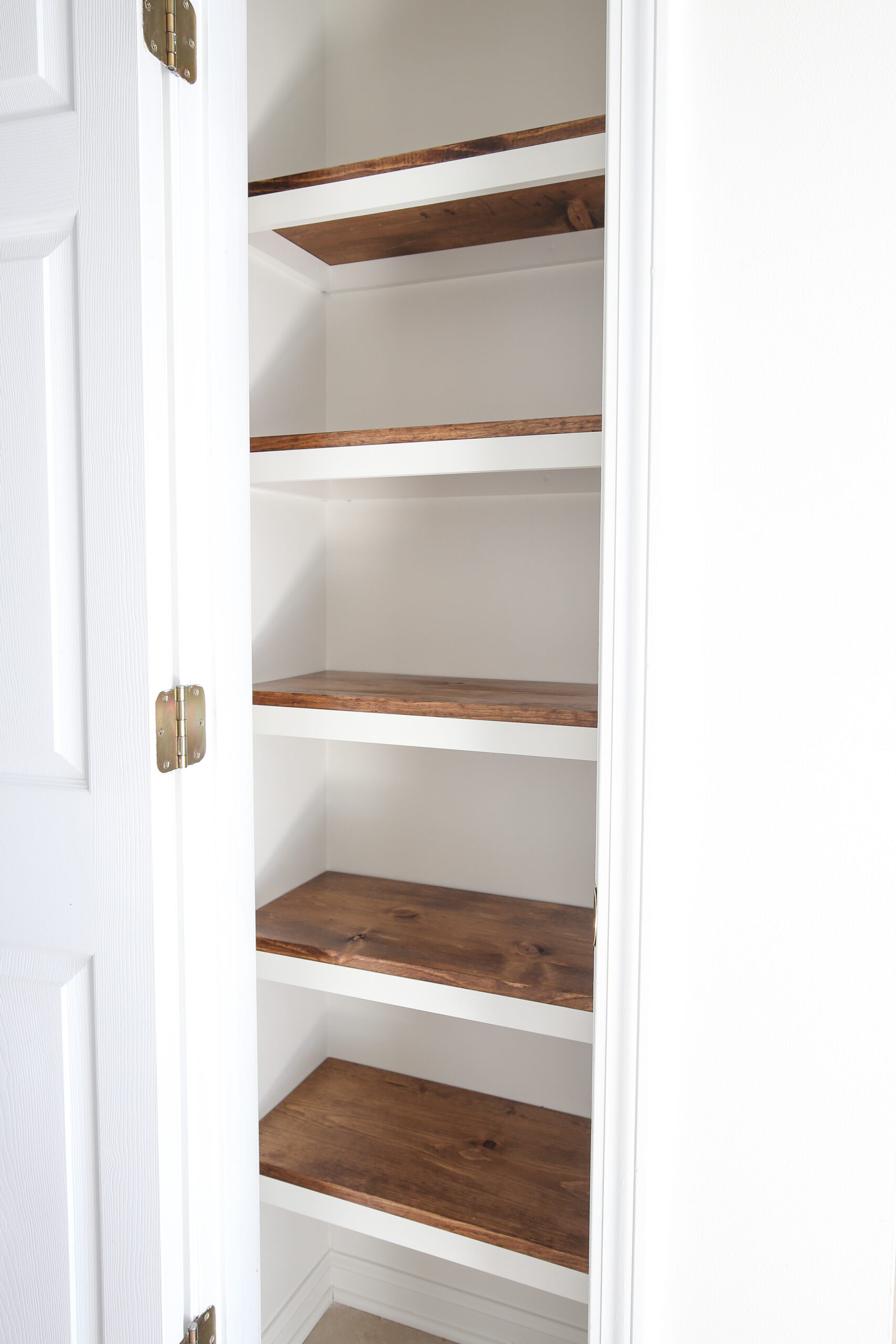 DIY Pantry Shelves with stained wood shelves and painted white trim