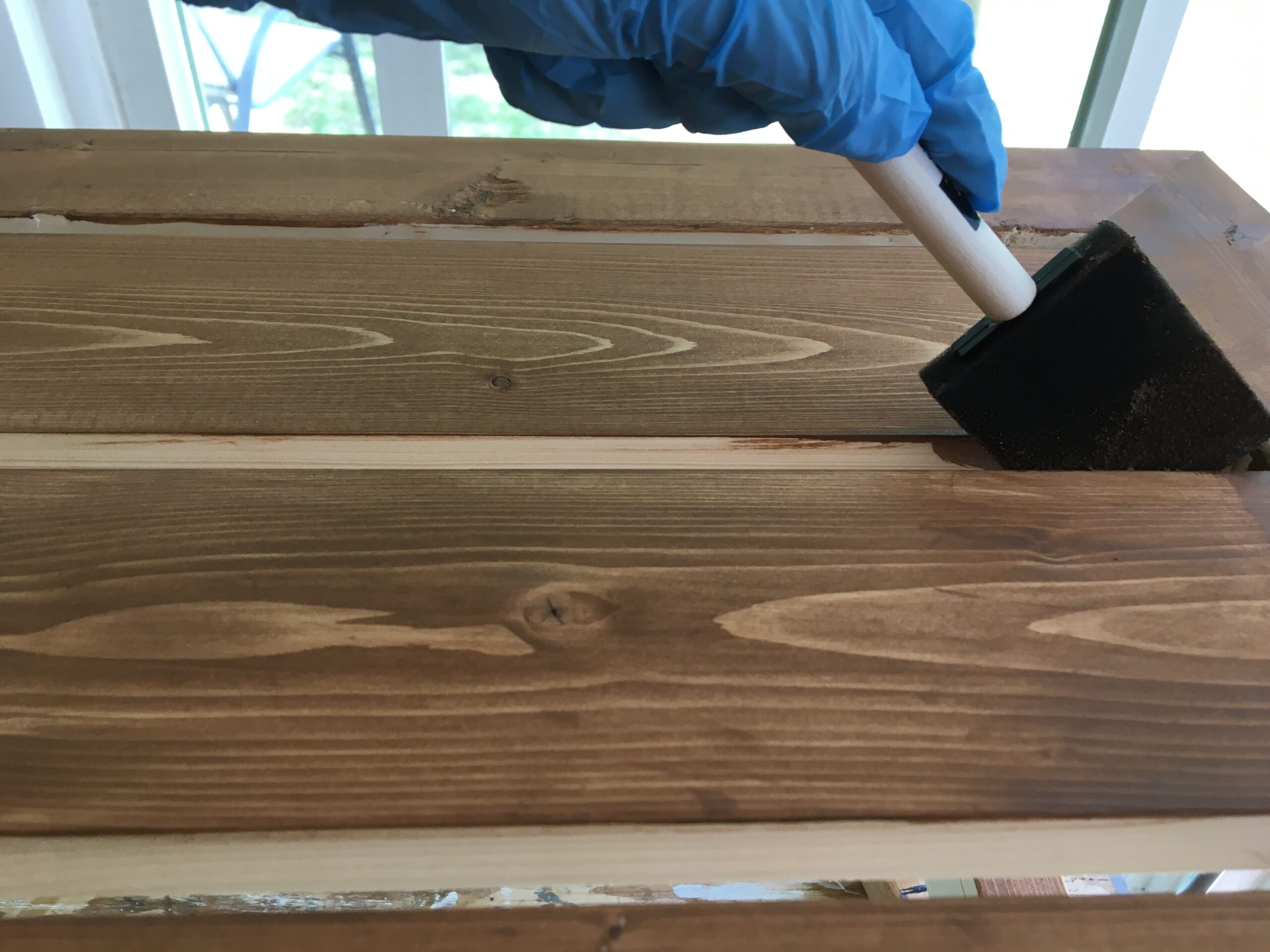 staining between wood slats with a foam brush