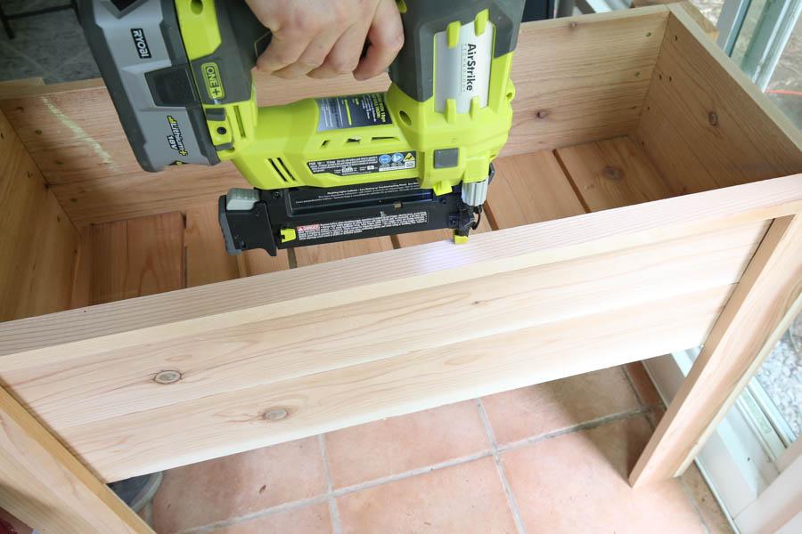 Add 1x2 trim to top of diy raised planter box