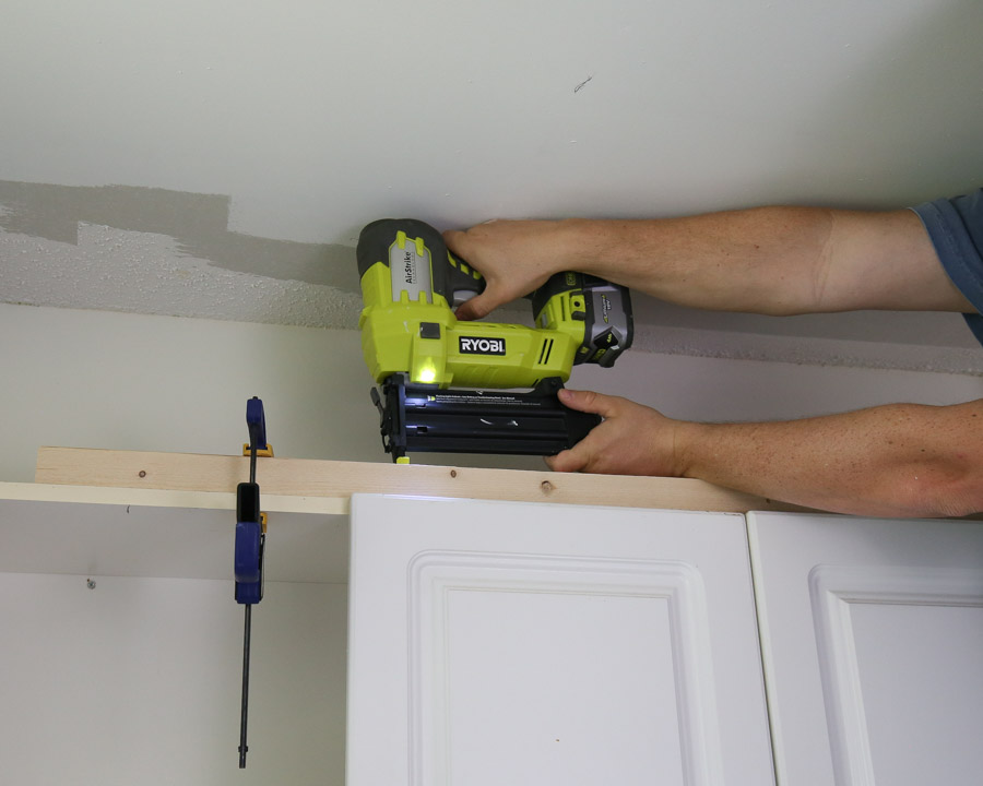 "Add a 2x2 board to the top of your cabinets with 2"" brad nails and a brad nailer"