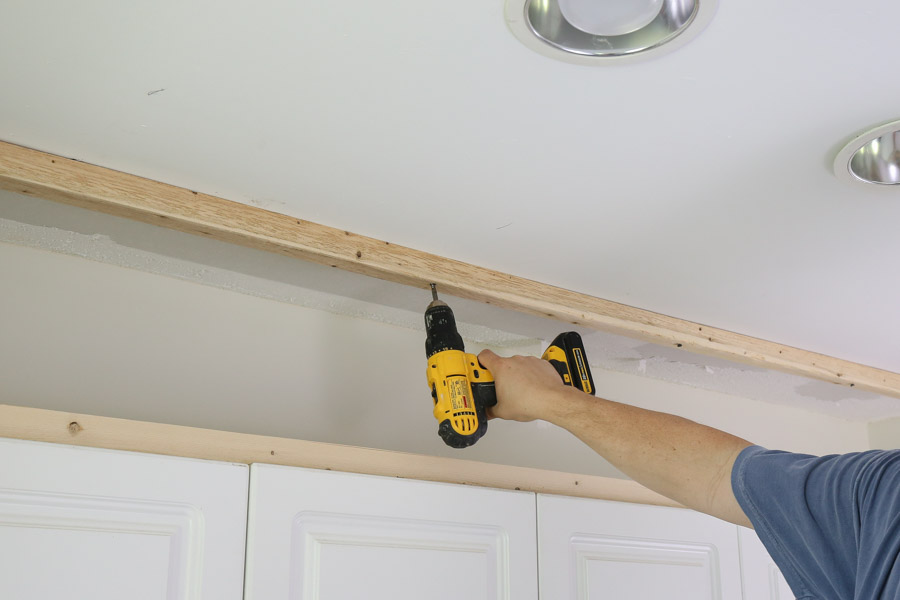 use screws and drill to attach wood board into ceiling studs above cabinets