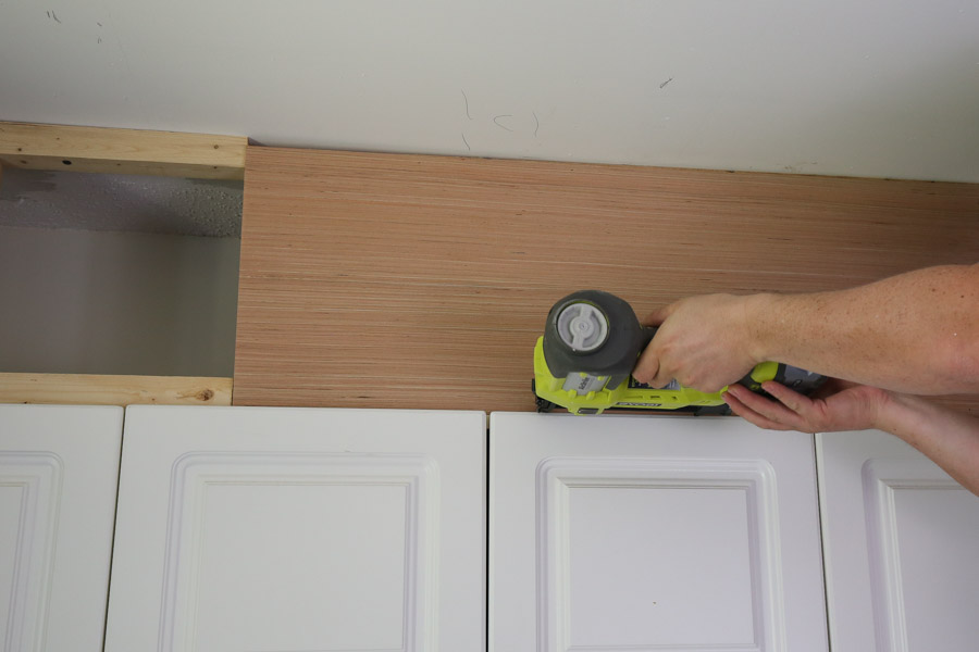 attach plywood to 2x2s to close space above cabinets