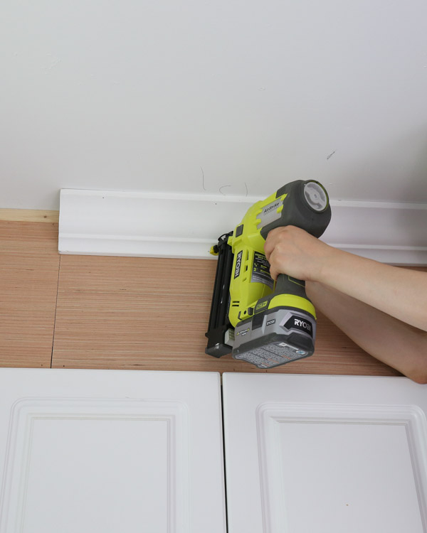 attach crown molding to ceiling and cabinet enclosure with brad nailer